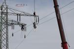 Auf eingehängten Leitern stehen die Monteure, um die Leiterseile von den Isolatoren zu lösen